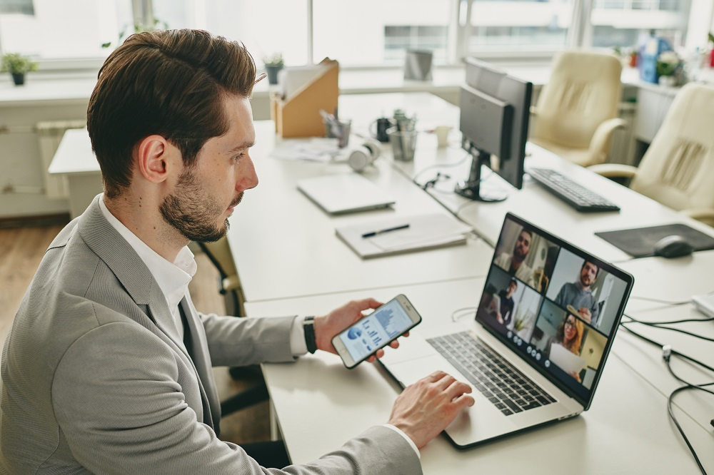 Image showing a business man on his phone and laptop video chatting with colleagues