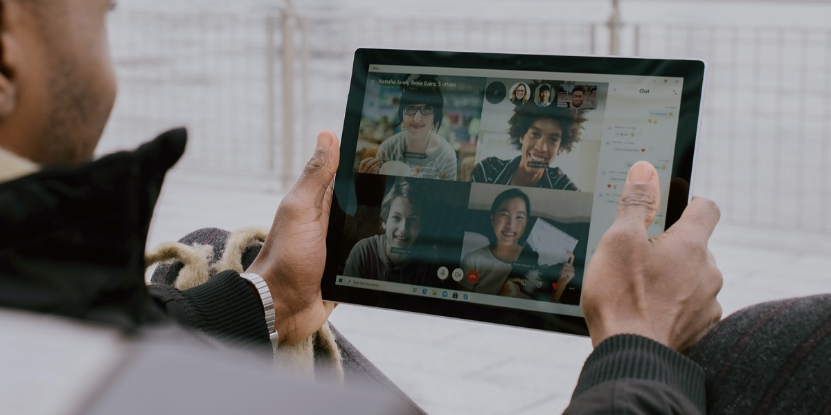 photo of a man using microsoft teams to communicate with his colleagues