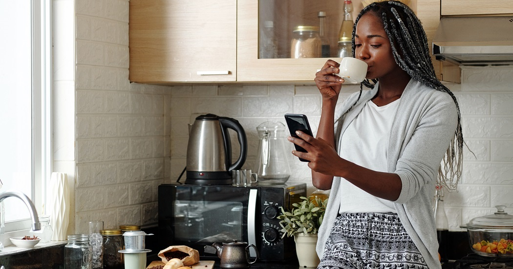 Woman reading news on her phone while drinking tea | Top tips for looking after mental health as we leave lockdown