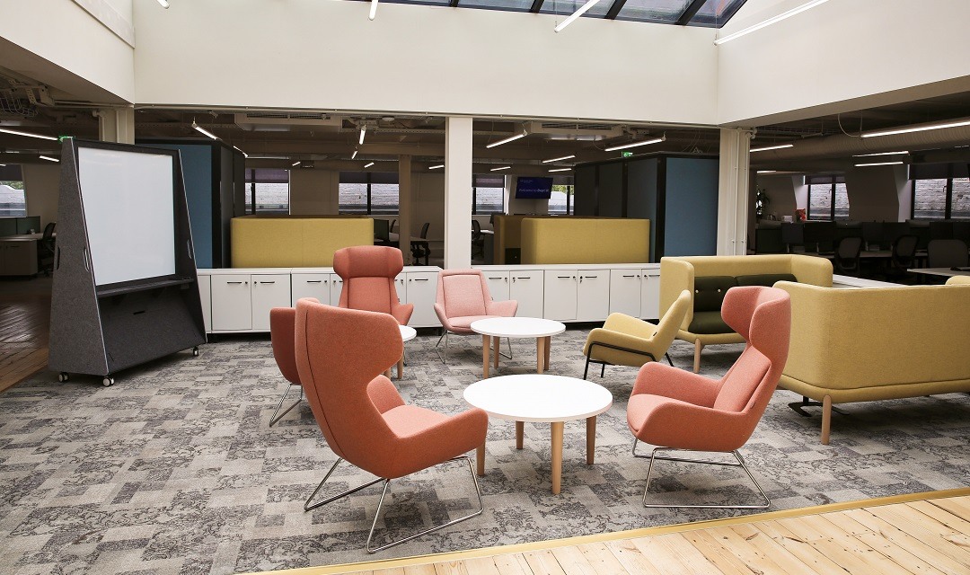 Photo of a modern working space at Department W - orange chairs, grey floorings and a light, bright space.